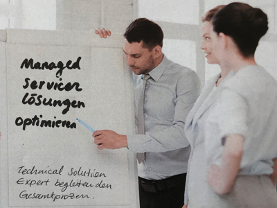 Eine Gruppe steht vor einer Flipchart-Präsentationstafel, wobei ein Mann rechts von der Tafel auf einen Punkt der