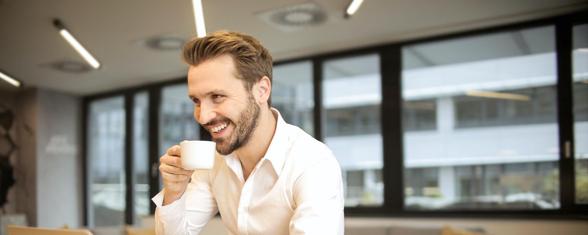 Man sitting at his laptop drinking coffee