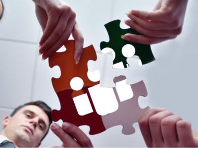 Ein von unten aufgenommenes Bild zeigt vier Personen welche jeweils ein Puzzleteil in die Mitte des Bildes halten, wobei sich ein Teil nähert, während die anderen schon eingefügt sind.