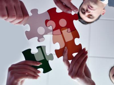 Ein von unten aufgenommenes Bild zeigt vier Personen welche jeweils ein Puzzleteil in die Mitte des Bildes halten, wobei sich ein Teil nähert, währund die anderen schon eingefügt sind.