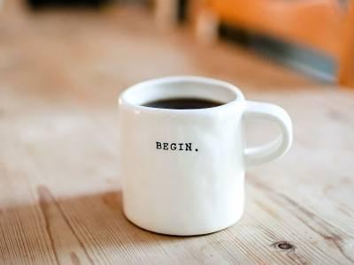 """Tisch mit Kaffeetasse, auf der """"Begin"""" steht"""