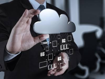 Eine Person hält mit der rechten Hand eine plastische Cloud (Wolke) aus welcher technische mobile Endgeräte angedeutet herausfallen.
