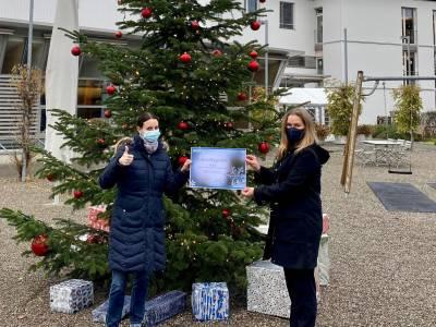 Zwei Frauen stehen vor einem geschmückten Tannenbaum, in der Hand ein Spendengutschein über 1000 CHF