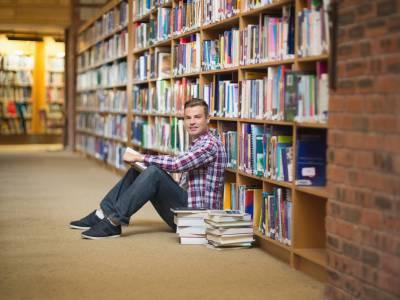 Ein Student, der vor einem Bücherregal auf dem Boden sitzt und in die Kamera lächelt.