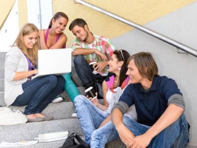 Studenten, welche gemeinsam auf einer Treppe sitzen und auf ein Laptop schauen.