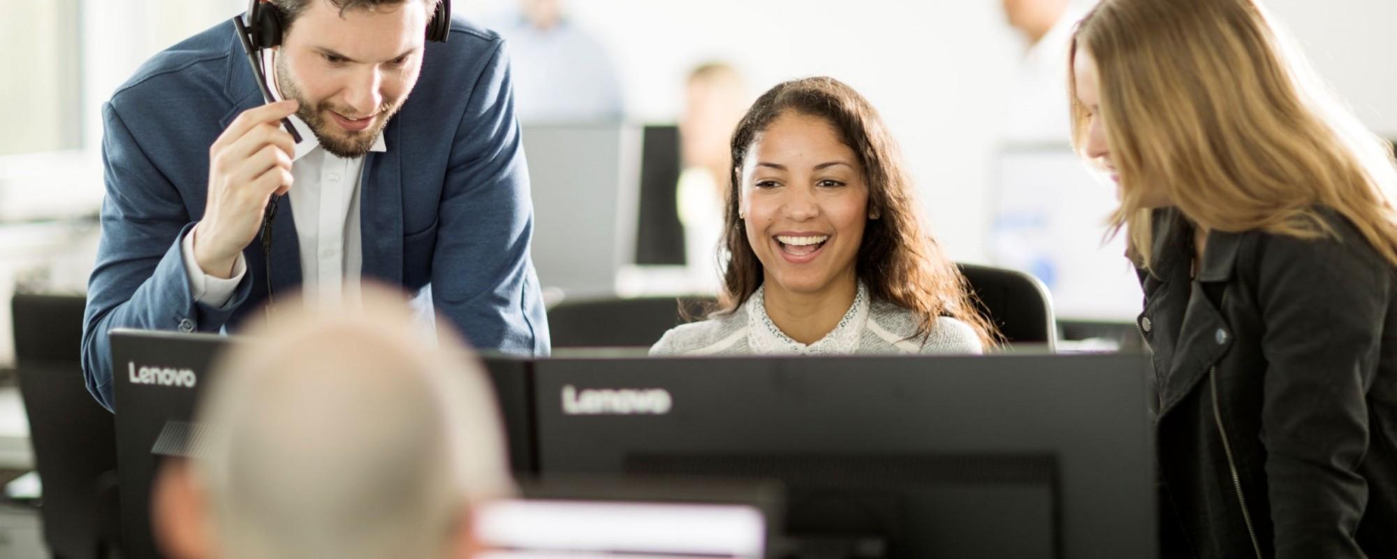 Drei Arbeitskollegen die zusammen vor einem Computer ein Gespräch halten.