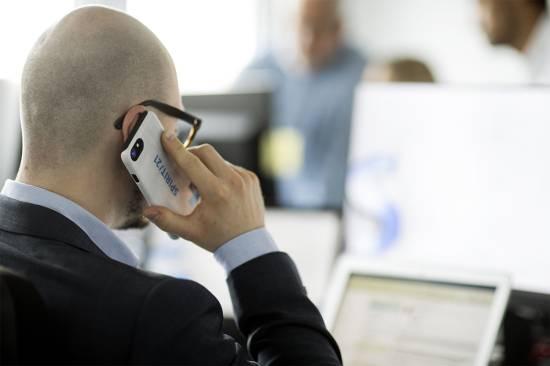 Ein Mann, der an seinem Laptop arbeitet und gleichzeitig sein Smartphone an sein Ohr hält.