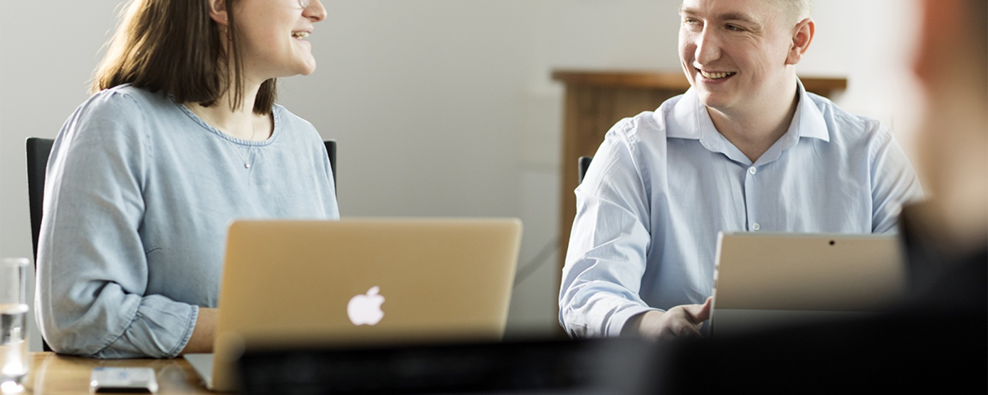 Eine Frau und ein Mann sitzen vor ihren Laptops und führen ein Gespräch.