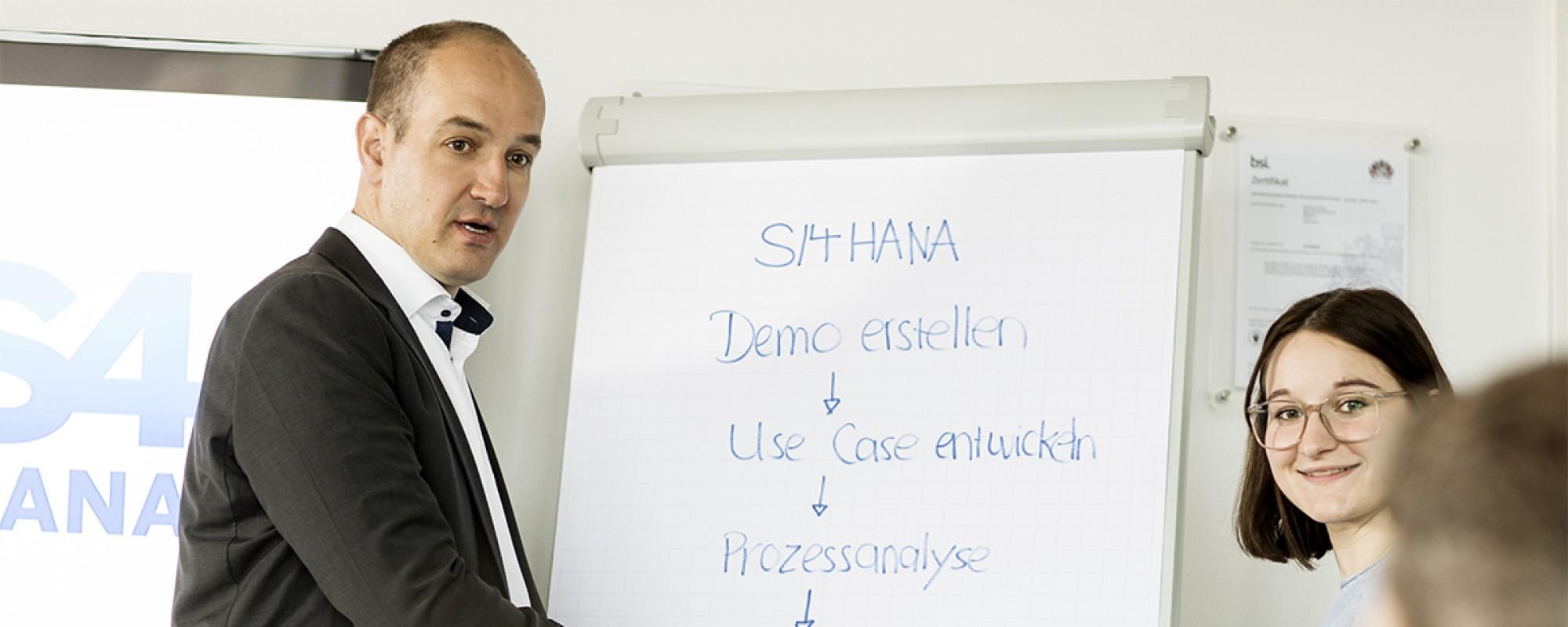 Ein Mann und eine Frau stehen vor einem Whiteboard und halten eine Präsentation über das Thema S/4HANA.