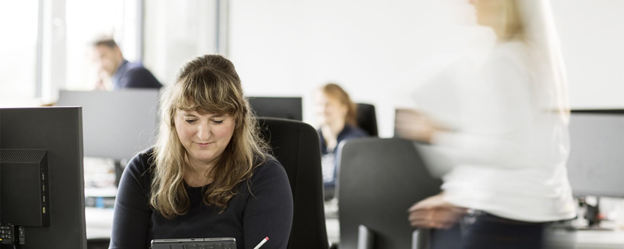 Eine Frau arbeitet in einem voll besetzten Büro an ihrem iPad.