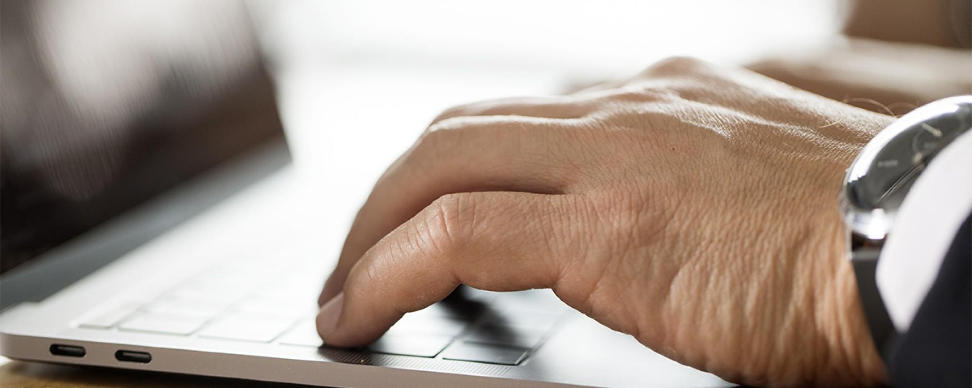 Ein Closeup Foto von einer Laptoptastatur, mit Händen welche darauf tippen.