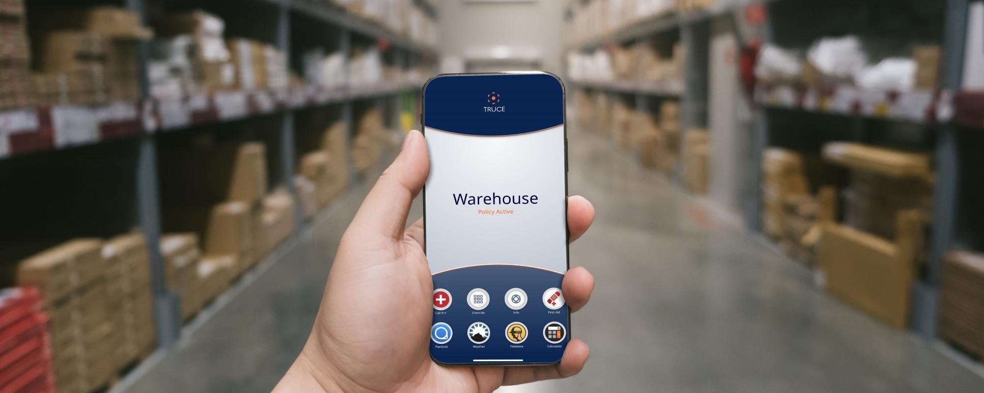 Eine Person hält ein Handy in einer Lagerhalle vor sich.